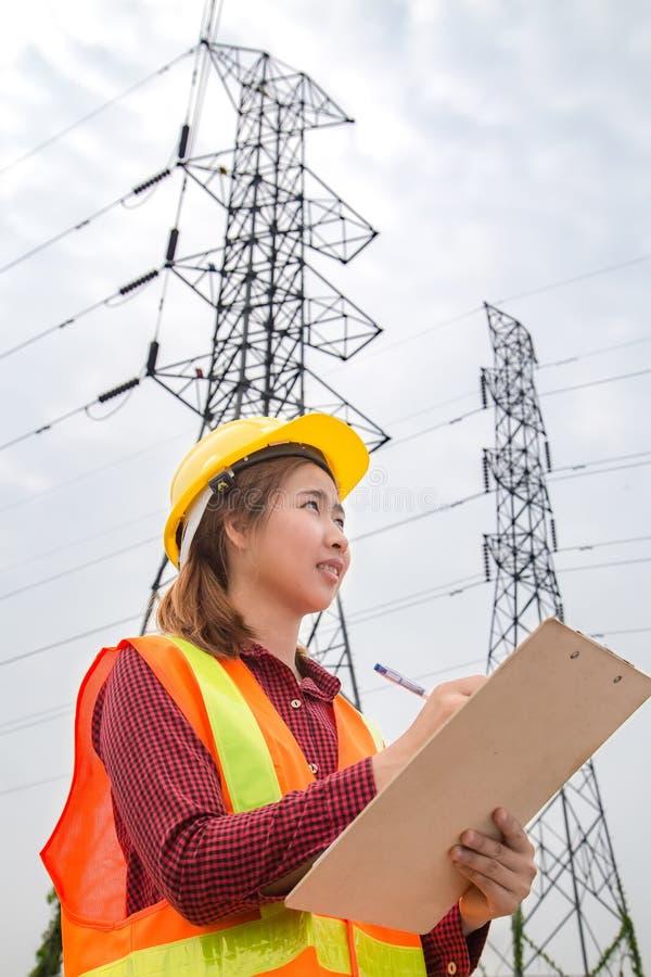 Ingénierie de femme travaillant à la tour à haute tension photo libre de droits