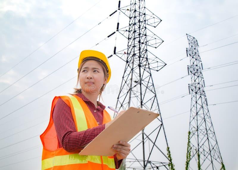 Ingénierie de femme travaillant à la tour à haute tension photos stock