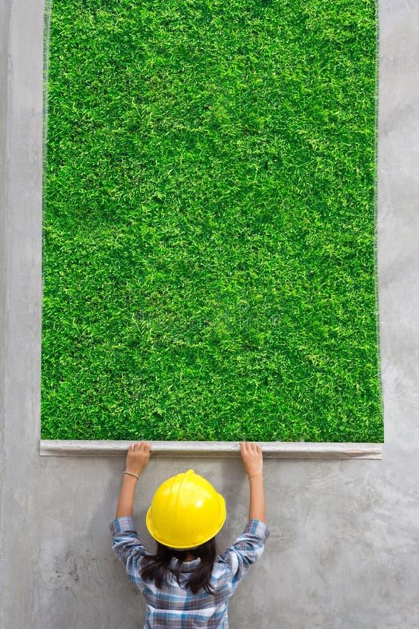 Ingénierie de petite fille avec peindre la texture d'herbe verte sur le mur image stock