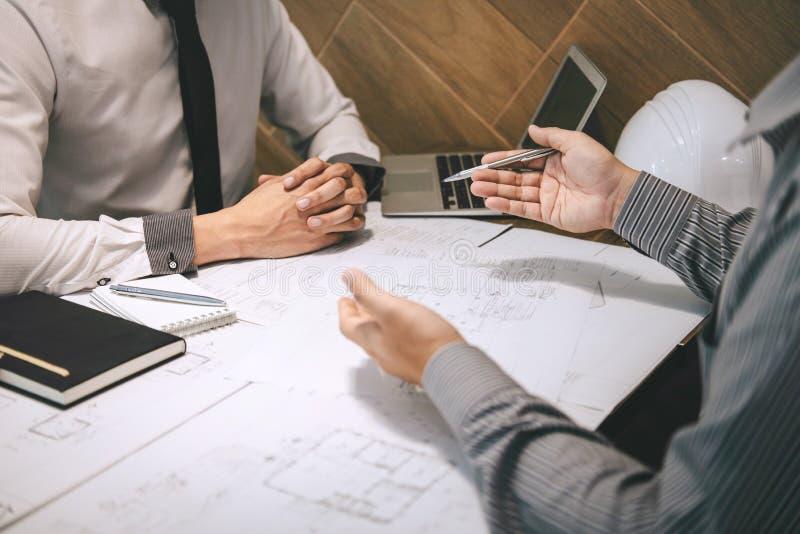 Ingénierie ou architecte de construction discuter un modèle tout en vérifiant l'information sur dessiner et esquisser, se réuniss photo libre de droits