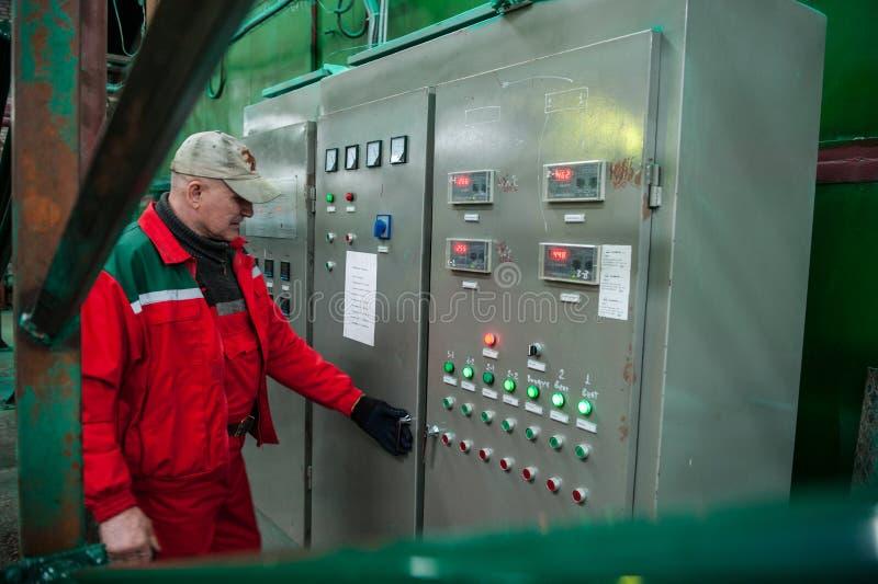 Ingénieur électrique à côté des contrôles de tableau de bord photographie stock libre de droits