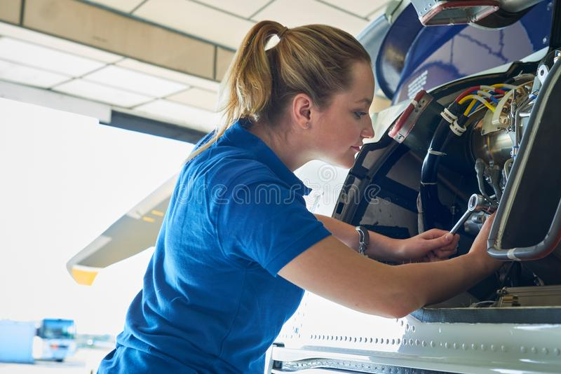 Ingénieur aérien féminin Working On Helicopter dans le hangar photographie stock libre de droits