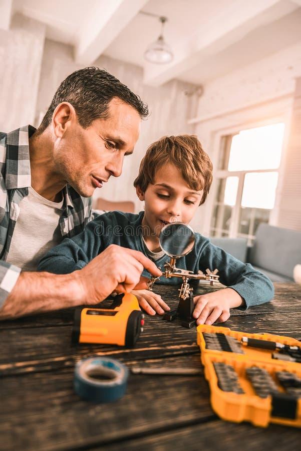 Ingénieur adulte responsable introduisant son fils dans le monde des instruments photographie stock libre de droits