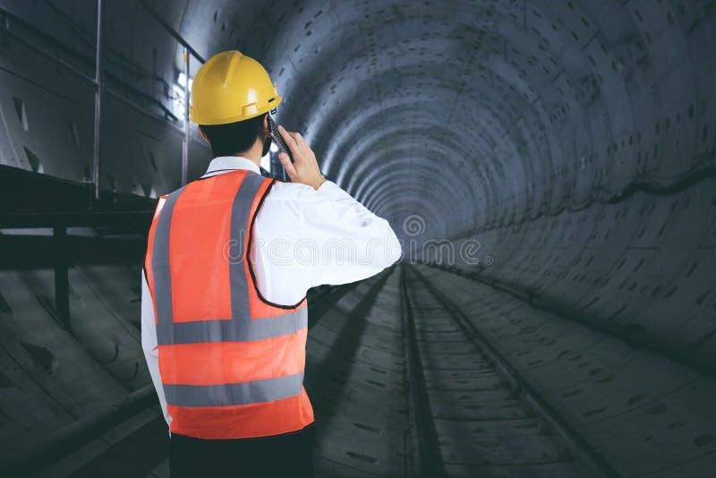Ingénieur avec le téléphone portable dans le tunnel image stock