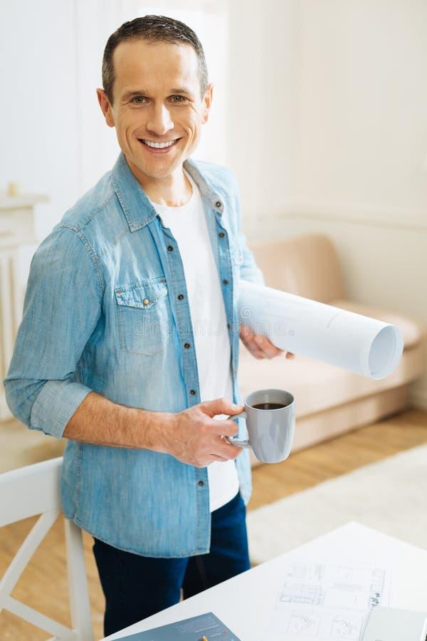 Ingénieur bel agréable se sentant ravi tout en se tenant avec une tasse de thé photographie stock