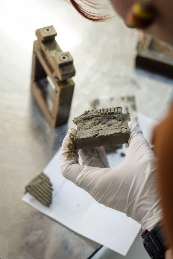 Ingénieur civil exécutant un essai en laboratoire pour la détermination de résistance au cisaillement et observant le sol après e image libre de droits