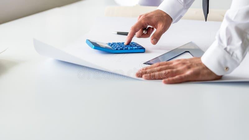 Ingénieur d'affaires calculant utilisant la calculatrice images libres de droits
