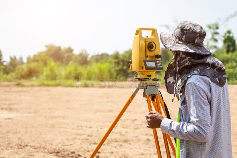 Ingénieur d'arpenteur faisant la mesure à la terre photographie stock
