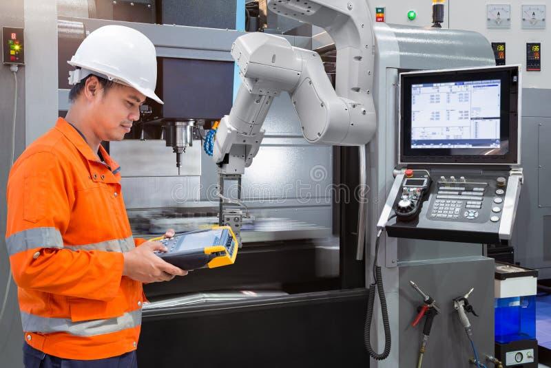 Ingénieur d'entretien programmant la main robotique automatique avec la commande numérique par ordinateur image libre de droits