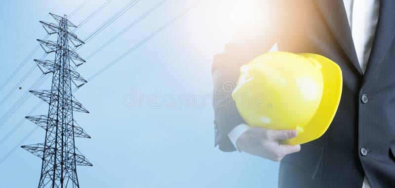 Ingénieur de double exposition avec le casque de sécurité sur le poteau à haute tension photo libre de droits
