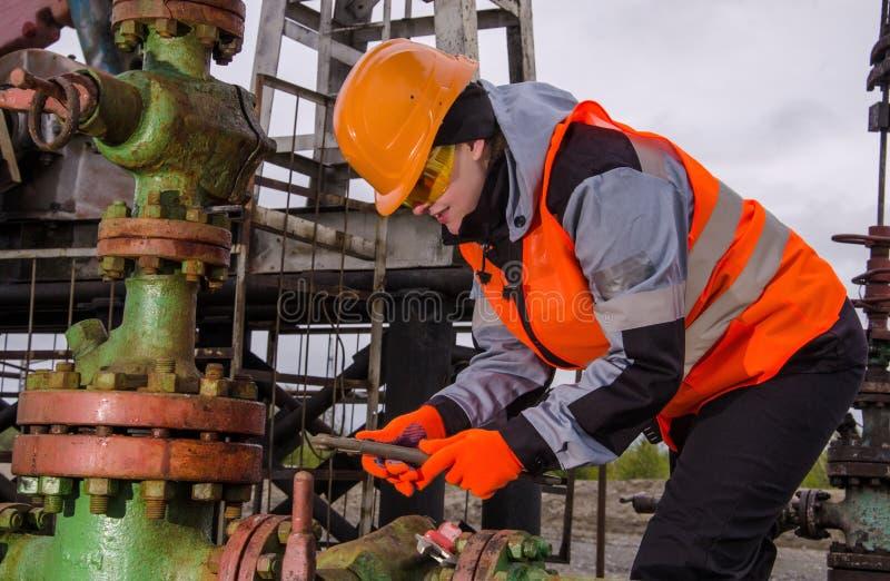 Ingénieur de femme dans le gisement de pétrole réparant la tête de puits photographie stock