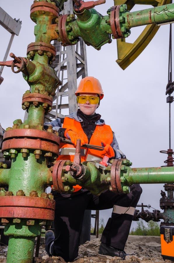 Ingénieur de femme dans le gisement de pétrole réparant la tête de puits photo libre de droits