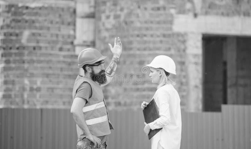 Ingénieur de femme et constructeur brutal barbu discuter le progrès de construction Gestion des projets de construction Construct photographie stock