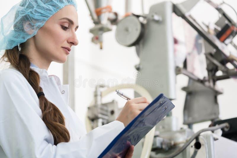 Ingénieur de femme rédigeant le rapport technique tout en dirigeant le manufa photographie stock