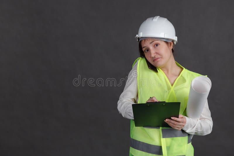 Ingénieur de jeune femme dans le casque de protection et gilet parlant au téléphone et prenant des notes encombrement photos libres de droits