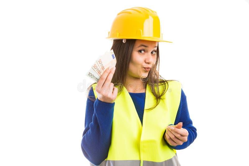 Ingénieur de jeune femme tenant le salaire photo stock