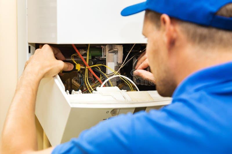 Ingénieur de service de maintenance travaillant avec la chaudière de chauffage au gaz images stock