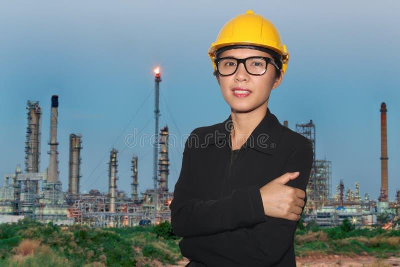 Ingénieur des femmes dans le sourire sur le fond de crépuscule de raffinerie de pétrole images stock