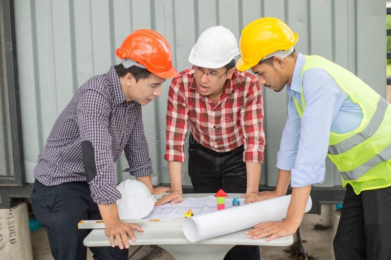 Ingénieur et équipe de construction regardant le modèle et parler du procédé de construction photographie stock libre de droits