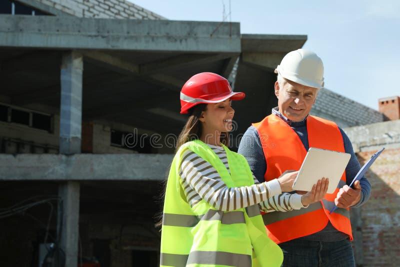 Ingénieur et agent de maîtrise professionnels dans le dispositif de protection avec le comprimé au chantier de construction images stock