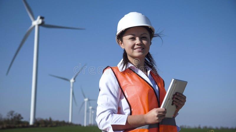 Ingénieur féminin de sourire se tenant contre la ferme de vent photos stock