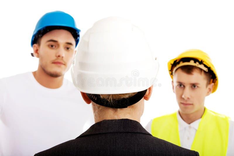 Ingénieur féminin parlant avec deux constructeurs photographie stock libre de droits