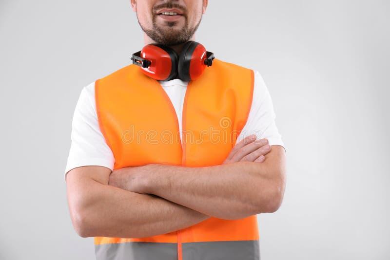 Ingénieur industriel masculin dans l'uniforme sur le fond clair, plan rapproché images stock