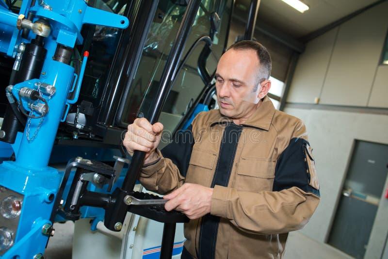 Ingénieur masculin actionnant des machines de commande numérique par ordinateur dans l'usine photo stock