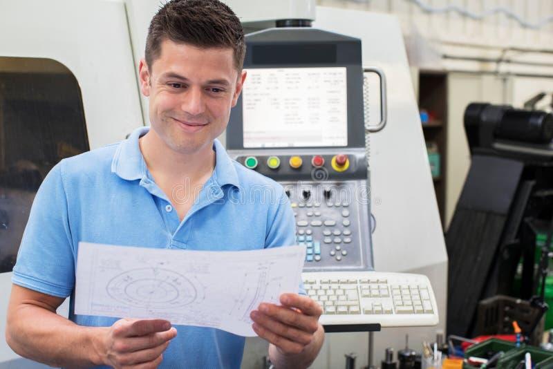 Ingénieur masculin With Technical Drawing actionnant la machine de commande numérique par ordinateur dans le fa photographie stock libre de droits