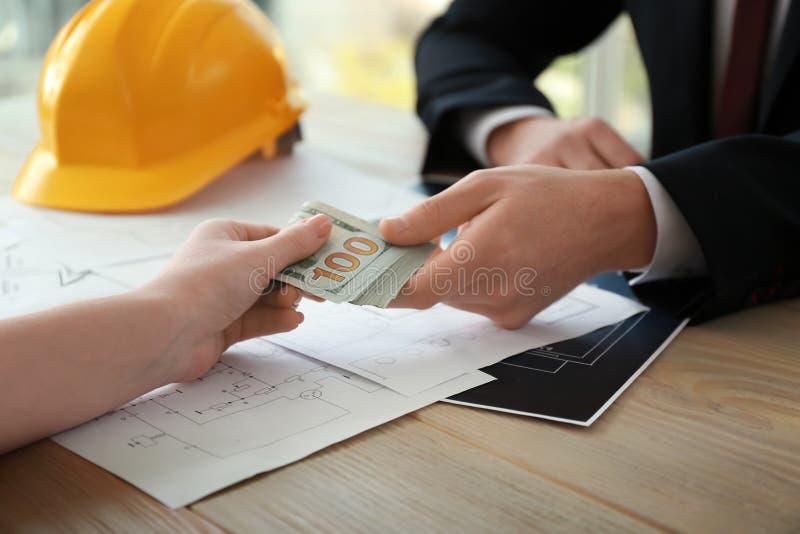 Ingénieur prenant le paiement illicite de la femme à la table Concept de corruption image libre de droits