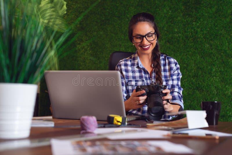 Ingénieur regardant les photos qu'elle a prises sur la caméra qui matin photos stock