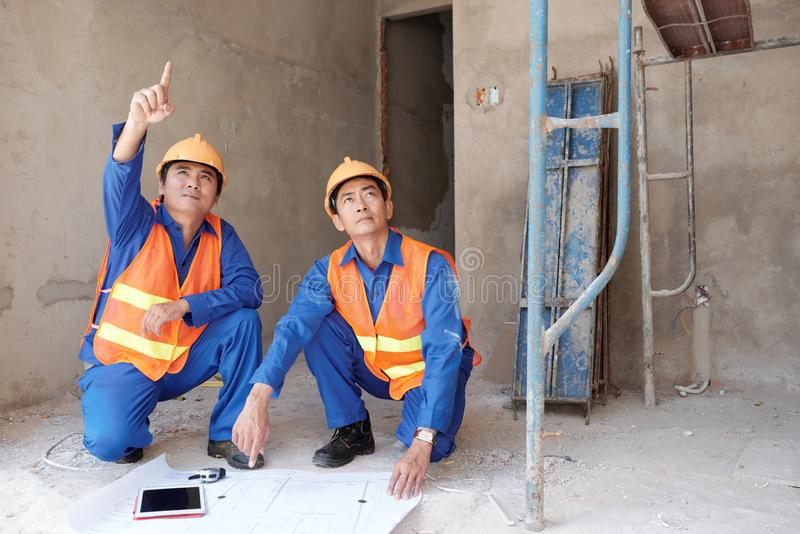 Ingénieurs à l'intérieur du bâtiment en construction photo stock