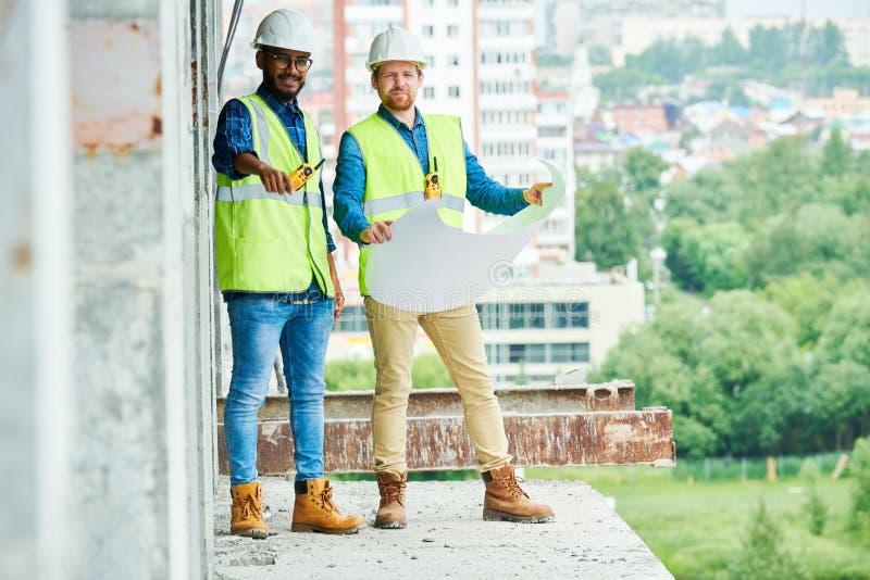 Ingénieurs avec l'ébauche inspectant le chantier de construction images libres de droits