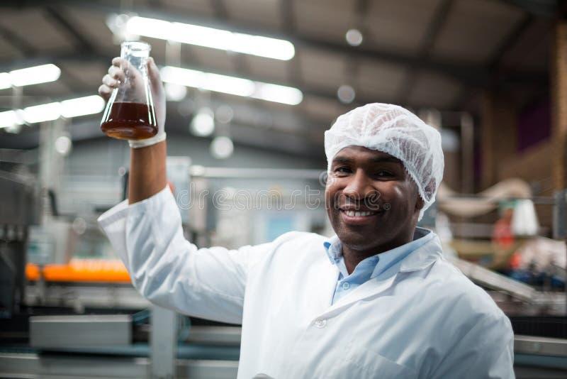 Ingénieurs d'usine tenant un échantillon de boisson image stock