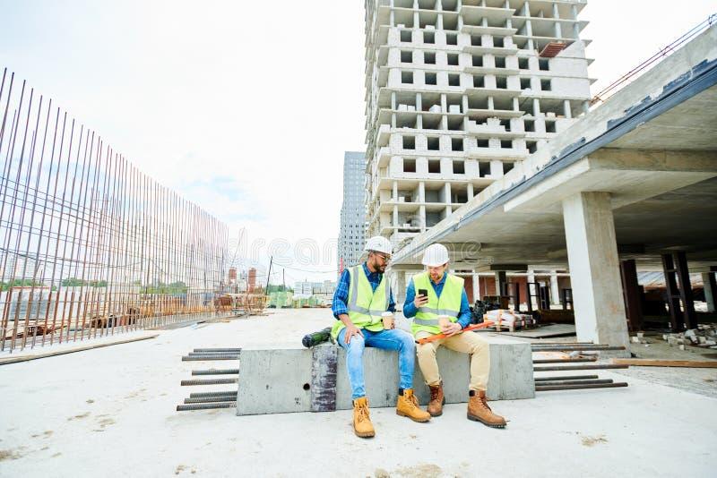 Ingénieurs de construction avec le smartphone pendant la coupure photographie stock libre de droits