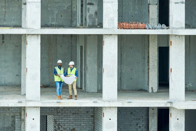 Ingénieurs de construction lisant l'ébauche dans le bâtiment non fini photo libre de droits