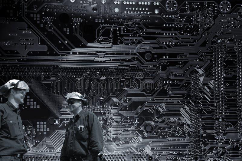 Ingénieurs de technologie et pièce géante d'ordinateur photo stock