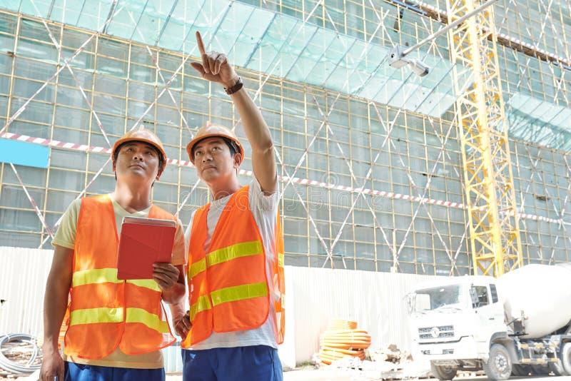 Ingénieurs discutant le travail dehors photos libres de droits