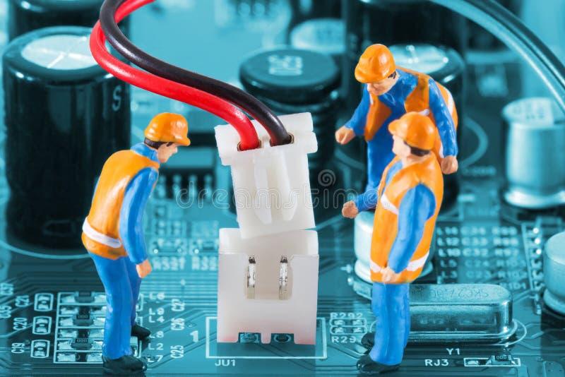 Ingénieurs miniatures fixant le connecteur de fil photographie stock libre de droits