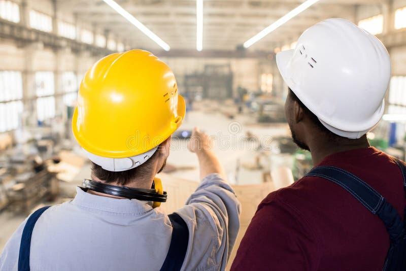 Ingénieurs qualifiés visualisant le croquis au chantier de construction photo stock