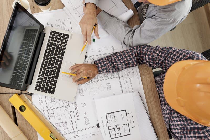 Ingénieurs recueillis à l'ordinateur portable pour la réunion quotidienne photo libre de droits