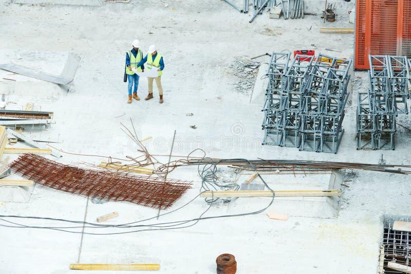 Ingénieurs sur le modèle de lecture sur le chantier de construction image stock