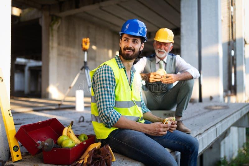 Ing?nieur m?r et jeune heureux, architecte, travailleur s'asseyant au chantier et repos photos stock