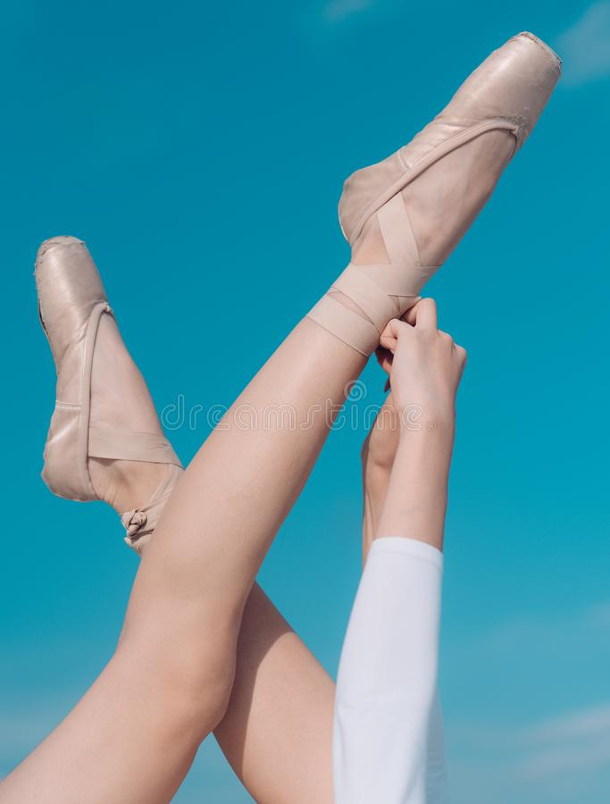 Touching the sky. Pointe shoes worn by ballet dancer. Ballet slippers. Ballerina shoes. Ballerina legs in ballet shoes stock image