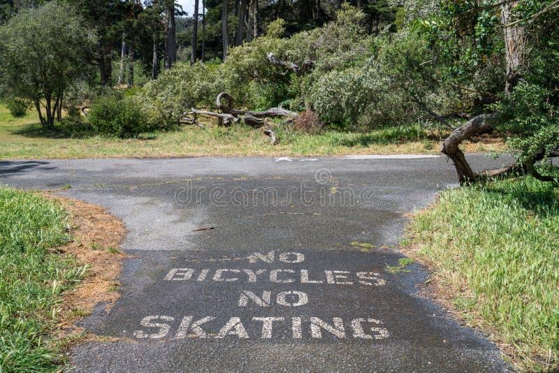 Inga cyklar ingen åka skridskor varning på asfalttrottoaren i stads- parkerar rekreationsområde royaltyfri bild