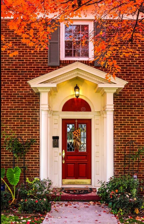 Ingang aan baksteenhuis met pijlers voor portiek en rode deur met autumbladeren op stoep en kleurrijke takken die beeld ontwerpen royalty-vrije stock foto's