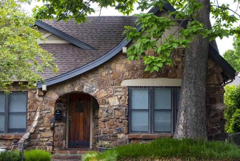 Ingang aan leuk die rotsplattelandshuisje door bomen met houten plankdeur en gras wordt omringd vooraan stock afbeelding