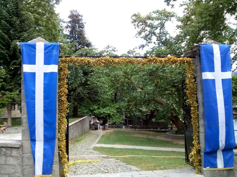 Ingang aan orhtodoxkerk van Agia Paraskevi in Metsovo, Epirus, Griekenland Griekse vlaggen stock foto