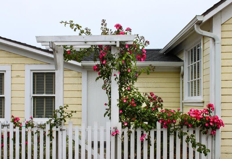 Ingang aan vrolijk geel houten huis met witte piketomheining en een poort met een as met wilde rozen die op en over het groeien stock fotografie
