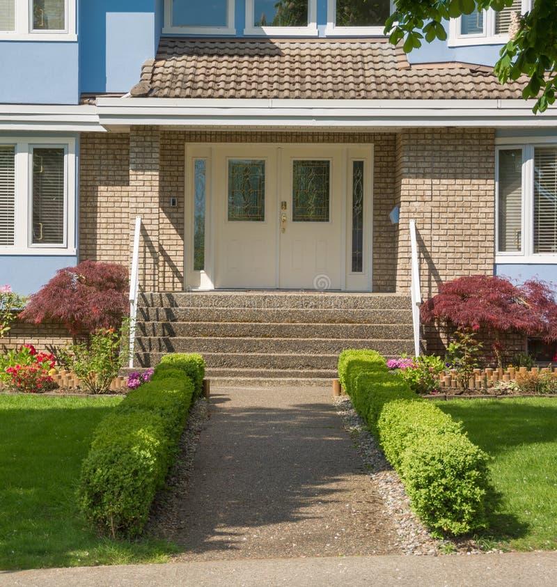 Ingang van familiehuis met kleine hagen aan kanten op gebied in de voorsteden stock afbeeldingen